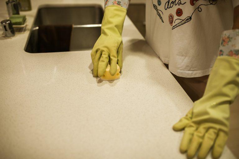 mains avec gants jaunes qui frotte avec une éponge