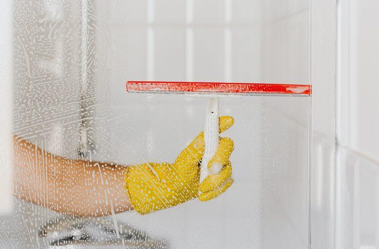 main avec gant jaune qui nettoie une vitre