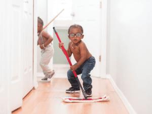 Petit qui fait le ménage avec un balai rouge