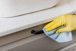 Main avec gant jaune qui frotte un tiroir avec une lavette microfibre bleue