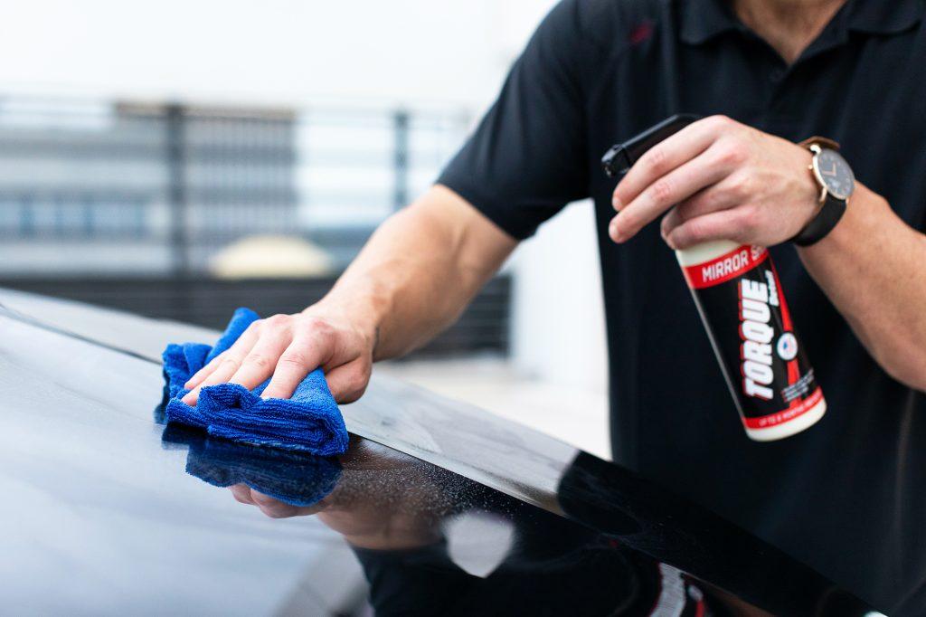 Main qui frotte un capot de voiture avec une lavette microfibre